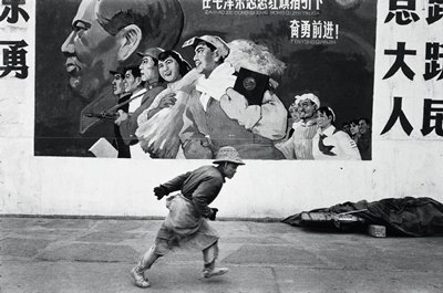 man wearing a straw hat, gloves and apron, running in front of a wall with a mural with male and female workers and soldiers