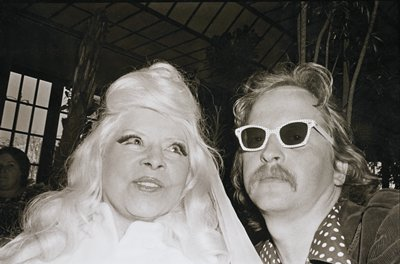 Mae West at L wearing long false eyelashes, white jacket and long blonde hair; Ramon Muxter at R with long hair and moustache, wearing polka-dot framed sunglasses, polka-dotted shirt and corduroy jacket; same image as 89.100.33