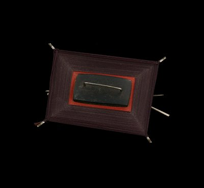 X-shaped silver frame with dark purple and red threads wrapped around frame to form two rectangles; central rectangle of dark ebony wood with silver bar at middle