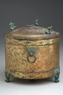 This covered cylindrical toilet box, supported by three small feet in the form of bears, is gilt with decor patterns executed in incised lines. there are two ring handles suspended from t'ao-t'ieh masks on the vessel and a third ring handle on the lid, which is further adorned by three birds, reduced and highly stylized, in the round. The neck and foot belts bordering the main decor band display the 'triple lozenge' figure common on the Huai style mirrors and immensely popular throughout the Han era. The scene portrayed on the body presents various animals- birds, deer, bears- moving through a field of hills and drifting clouds. the treatment is spirited and free, with nothing in it of the symmetry one de rigeur in the bronze decor. The long, fluid lines are adorned with the 'han curl border' (for comment see BMFEA, Volume 13, pages 97,98). Patina light green at feet and on the lid animals.