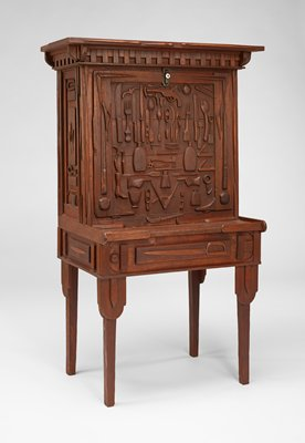 drop-front desk with four-legged base; front of base decorated with high-relief carving of sword; exterior of drop-front decorated with high-relief carvings of forks and knives, bottles, gun, various tools (saw, pick axe, trowel, shovel), pocket knives, two pointing hands and other objects; sides also decorated with applied relief carvings of various objects; medium wood patina