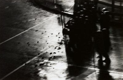 blurry image of group of shadowy figures wearing helmets at right on wet, shining pavement