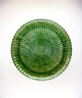 Spinach green jade, carved in chrysanthemum form, small flutings, spread in tiers from the center of the plate, representing the petals of the flower. Carved on both sides, the petals curled over the rim. The jade is extremely thin and translucent.
