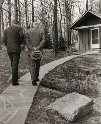 """two men wearing suits, seen from back, walking down a stone path to a small cabin with bare trees to left, with a sign reading """"DOGWOOD"""" above the door; older man at right carries a fedora hat in both hands held behind his back"""