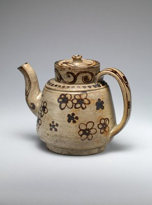 tea pot with raised neck and wide handle; black-brown design against beige background; cherry blossom motif on one side, willow branches on opposite side; tendril-like designs on spout and neck; spots around neck; petal-like lines and spots on lid