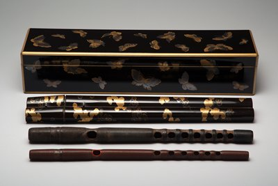 black lacquered box with gold and silver butterflies; double flute case in black lacquer with gold and silver clouds and dragon design on bottom; bamboo flute inside with dark ribbing; smaller flute with red ribbing and details, both stored in double case; single bamboo flute case in plain wood with gold inscription on one side; also comes with two documents in handscroll form depicting the flute's history; document dated 1774