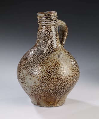 Stoneware (Greybeard type) all over mottled design of brown on grey. Beneth lip in front a grotesque mask of man, whose hair and beard are depicted by incised lines. Neck of jug reeded. Glaze unevenly applied.