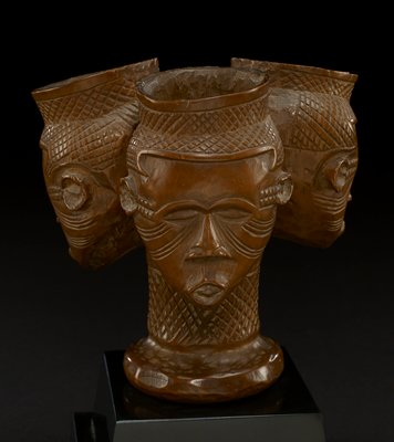 triple headed cup in natural honey-color of wood out of which it is carved; the top of the cups are straight and taper into the figure of a head; each cup rim is carved with crisscross pattern; the faces have eyebrows, closed eyes, triangular noses, and pursed lips; each face has carved lines that extend from the inside and outside corners of the eyes to behind the ears; two rows of carved squares create a pattern between the temples and ears on all faces; the heads connect at a long single neck, which widens at the bottom forming the base; the neck is carved with the same pattern as the pattern at the top of each head