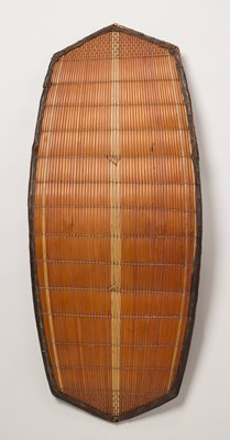 two-sided woven shield with tan wicker backing; dark brown wood border along outer edge; three vertical lighter brown strips of wicker in running lengthwise in center; single line of wicker on both right and left edges; slight convex curve in overall shape; wooden carved arm band in center on back