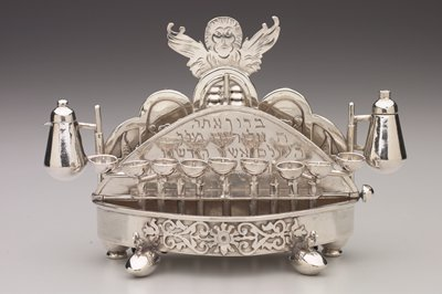 winged head above moveable doors flanked by lions and birds on back; bottom platform opens; candle cups on back at bottom; applied foliate decoration at front; Holiday Traditions, Judaica