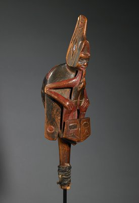 Chief's rattle; depicts the raven lengend a raven is shown with a human figure reclining on his back; the man holds a frog's tongue in his mouth in the act of sucking out a person which was believed to be helpful to shamans in their mystical rituals; the frog's body emerges from a hawk; the rounded underside of the raven's body is carved to represent a sparrow hawk; polychromed cedarwood sewn together with leather, inlaid abalone eyes in the raven