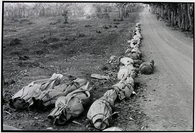 bodies wrapped in blankets and lining the side of a road