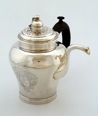 ginger jar-shaped body with capped swan neck spout; c-scroll handle with a knob on top and molded ring foot; cut-card work on cover; engraved coat of arms within scroll and foliate cartouche on front