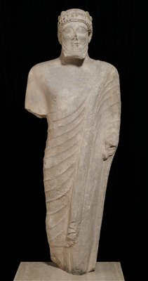 life-size carved statue of a bearded votary; In the archaic Cypriote style. The features show the mixed oriental style transformed by Hellenic influence; His head bears a wreath of leaves and berries permitting rows of small curls to frame his forehead. The beard is rendered in four stiff rows of curls. The skin tight tunic has no pleats, and the cloak which falls from the left shoulder is thrown over the left arm. Beard slightly defective. strong frontality and Greek 'archaic' smile