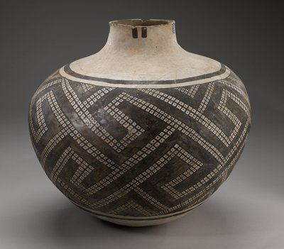 Tan vessel with a geometric design painted on with black pigment.