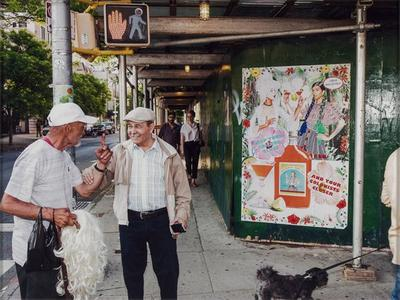 busy street scene; two men in conversation in LLQ, left figure holds black shopping bag and wig with white hair in PR arm; PL hand raised in the air, gripped by right figure, who wears a tan jacket and hat, with gray mustache and smiling; covered sidewalk in center with two figures walking under covering, female figure in right wearing black pants, glasses and white striped shirt, and is talking to a male figure wearing glasses, plaid button up shirt and baseball hat; colorful advertising sign on right depicting two costumed women, saluting with drinks; traffic crossing sign in ULC