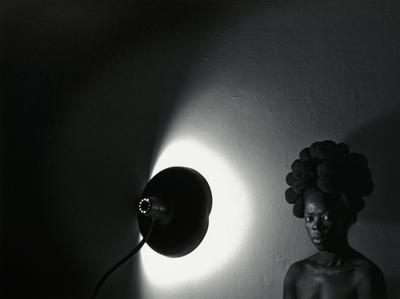 black and white image of head and shoulders of black woman with tall lobed hairstyle in LRC in front of a wall with a lamp at center