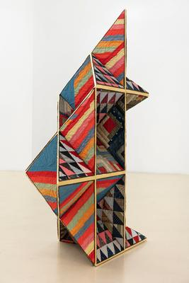 vertical geometric sculpture made up of triangular and square planes; faces of planes are covered in old patchwork quilts--triangular pieced designs with various printed fabrics, portion of Log Cabin pattern with various prints and some solid fabrics (particularly red and white), and solid colored diamond shaped pieces designs forming brightly-colored bars with larger solid blue areas; planes edged in gold leaf