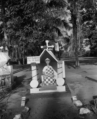Black and white photograph of a statue of a seated man with a checkered drapery over his lap within a small shrine