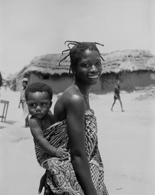 Black and white photograph of a woman with a baby on her back