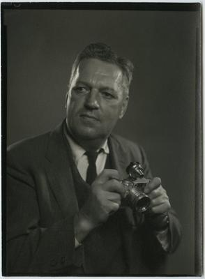 Black and white photograph of a man wearing a suit holding a camera and looking to the viewer's left