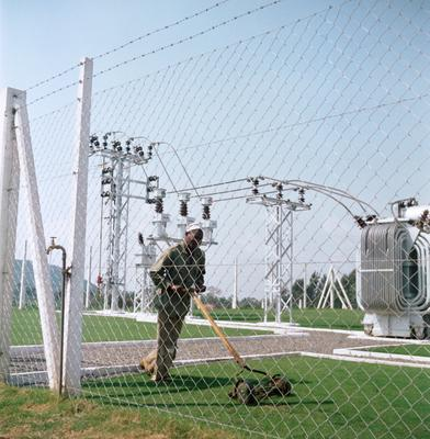 Color photograph of a man using a push-type mower to mow grass inside a fence with electrical towers behind him