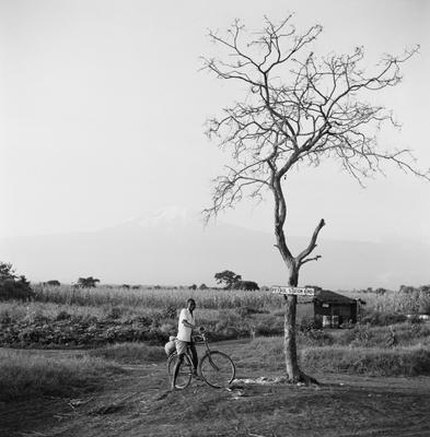 "Black and white image of a man on a bike under a tree with a sign on it that says ""Petrol Station Kindi"""