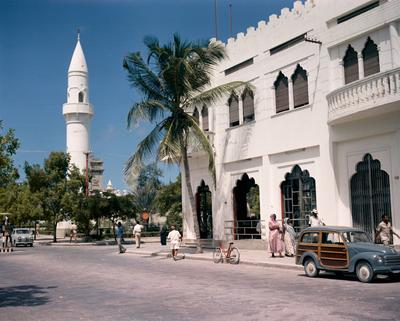 Color image of street scene; figures walk along the sidewalk; architecture in white with a minaret along the left side
