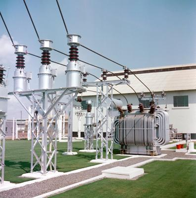 Color image of power plant equipment in an outdoor scene with neatly trimmed grass around it