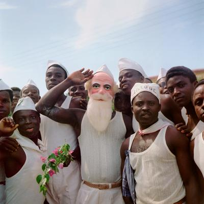Color image of a group of young men; the man at the center wears a Santa-like mask and salutes
