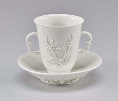 Cup (beaker) with flared sides and double scroll handles, flowering orange blossoms on the side.