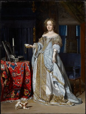 Portrait of a woman. Dutch golden age. A lady about thirty-four years of age with her fair hair in curls, stands full length at her toilet table, almost facing the spectator. She has a book in one hand and holds up her skirt with the other. She wears a light blue satin dress embroidered with gold lace. On the table, which is covered with a Turkey carpet, are a mirror, a silver box, and a candlestick. A spaniel frisks at her feet.