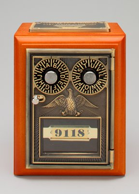 """orange-brown immitation wood; rectangular box; slot on top on immitation metal plaque with """"CREATED FROM ORIGINAL / POST OFFICE LOCKBOXES""""; immitation metal on front with 2 spinning letter combination locks, eagle and glass window with """"9118"""""""