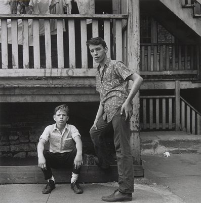 two boys in front of a porch; younger boy seated, older boy standing