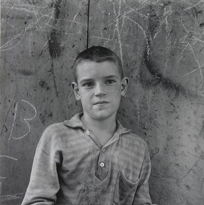 boy with short hair, dirty face and dirty shirt leaning against a wall with grafitti