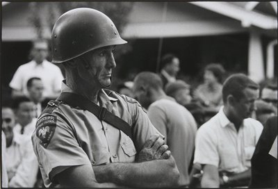 state patrolman with wrinkled neck and hands, wearing a helmet; other figures in background