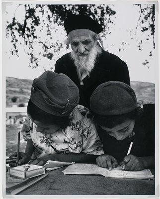 bearded elderly man in black hat standing behind children writing in book