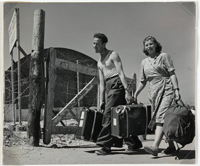 man and woman carrying suitcases past barbed wire gate