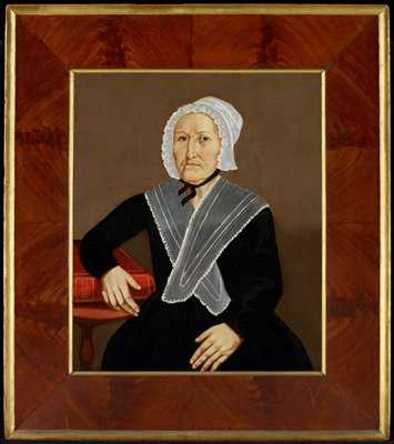 Portrait of a woman in black dress and white lace cap with grey wrap around her shoulders; PR elbow resting on Bible on table.