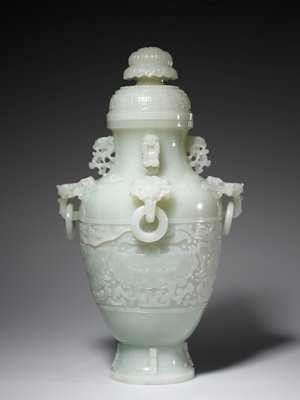 Vase, large, covered, white jade. Band of archaic animal design in relief on body. On the shoulders four archaic monster masks form ring handles from which are suspended loose rings; on the neck, above each handle, archaic birds in high relief. The cover, carved with a band of archaic animal design, is surmounted by a heavy lotus finial. On the low flaring base four shallowly incised flanges insipired by the .. Former Classification: Jade