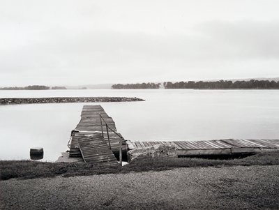 Old, broken-down docks; rocky sandbar extending toward center from left; trees visible on opposite shore