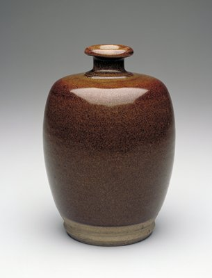 Egg-shaped bottle with brown teadust glaze; nearly flat shoulder; short neck with flaring, thick mouth; bottom section unglazed