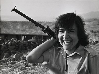 smiling woman with machine gun over her proper right shoulder