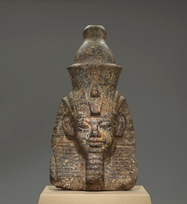 Head and shoulder of a pharaoh, wearing headgear; black and tan flecked marble; has own mount