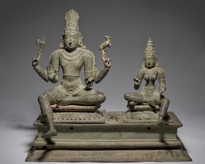 two seated figures, male and female, on separate bases that fit into large separate rectangular base; larger male figure has four arms and sits with PL leg drawn in and PR leg extended downwards at an angle; man wears headdress with wheel on back; one hand has a small animal perched on his fingers, another hand has a small axe-like object resting on fingers; female figure seated in mirror image of man's position, with a small bolster under PR knee; woman is bare-breasted and hold PL hand out, palm up; woman wears a tiered conical headdress with a wheel on the back