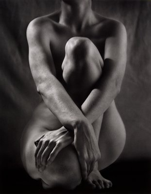 nude woman seated with PL knee up and hands crossed over PR knee