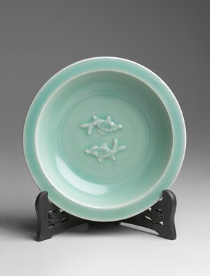 Bowl, shallow, with rim, of celadon ware from the Lung-Ch'uan district. The bottom is decorated with two fish in relief under the glaze, and the outside of the body is carved in a design of leaves. Thick, translucent bluish-green glaze on a body of greyish-white clay which shows through at edges where glaze is thin. The unglazed rim of the foot is a rusty brown, indicating the presence of iron in the clay