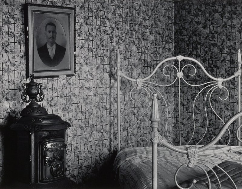iron bed in corner of room with floral wallpaper; heat stove at left with photograph of man above it on wall