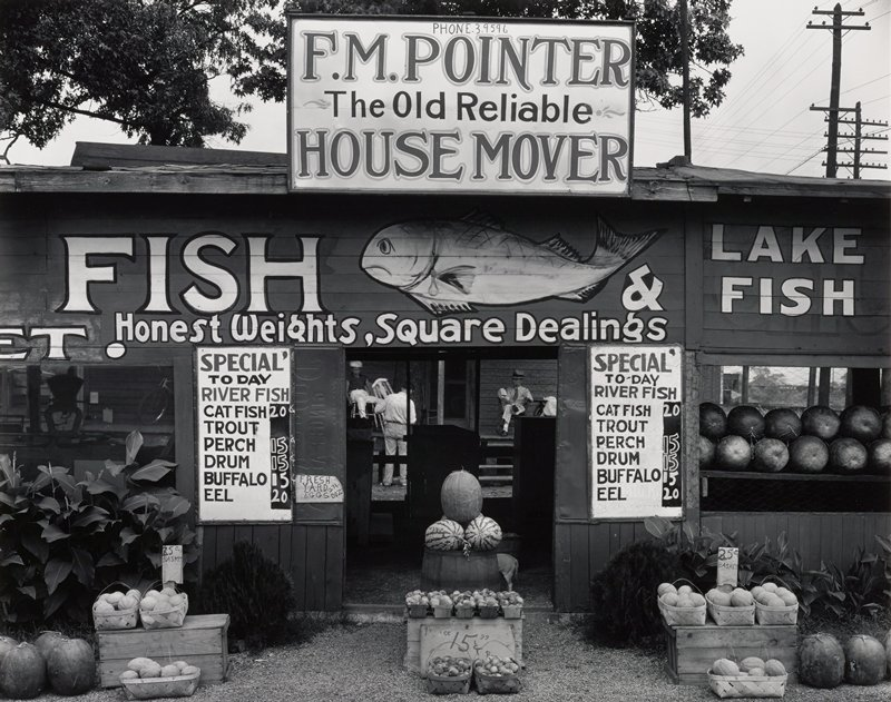 market stand with signs including painted fish; baskets of peaches and melons and stacks of watermelons; figures visible through doorway