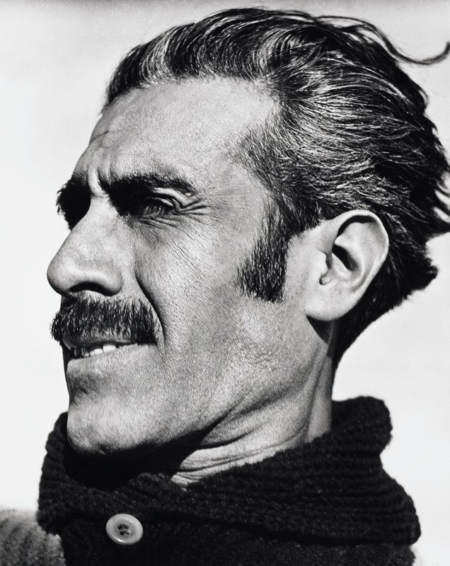 portrait of a man, head turned slightly to PR; man has dark wavy hair and moustache and wears a high-necked sweater